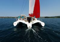 stern view of trimaran multihull yacht sailing