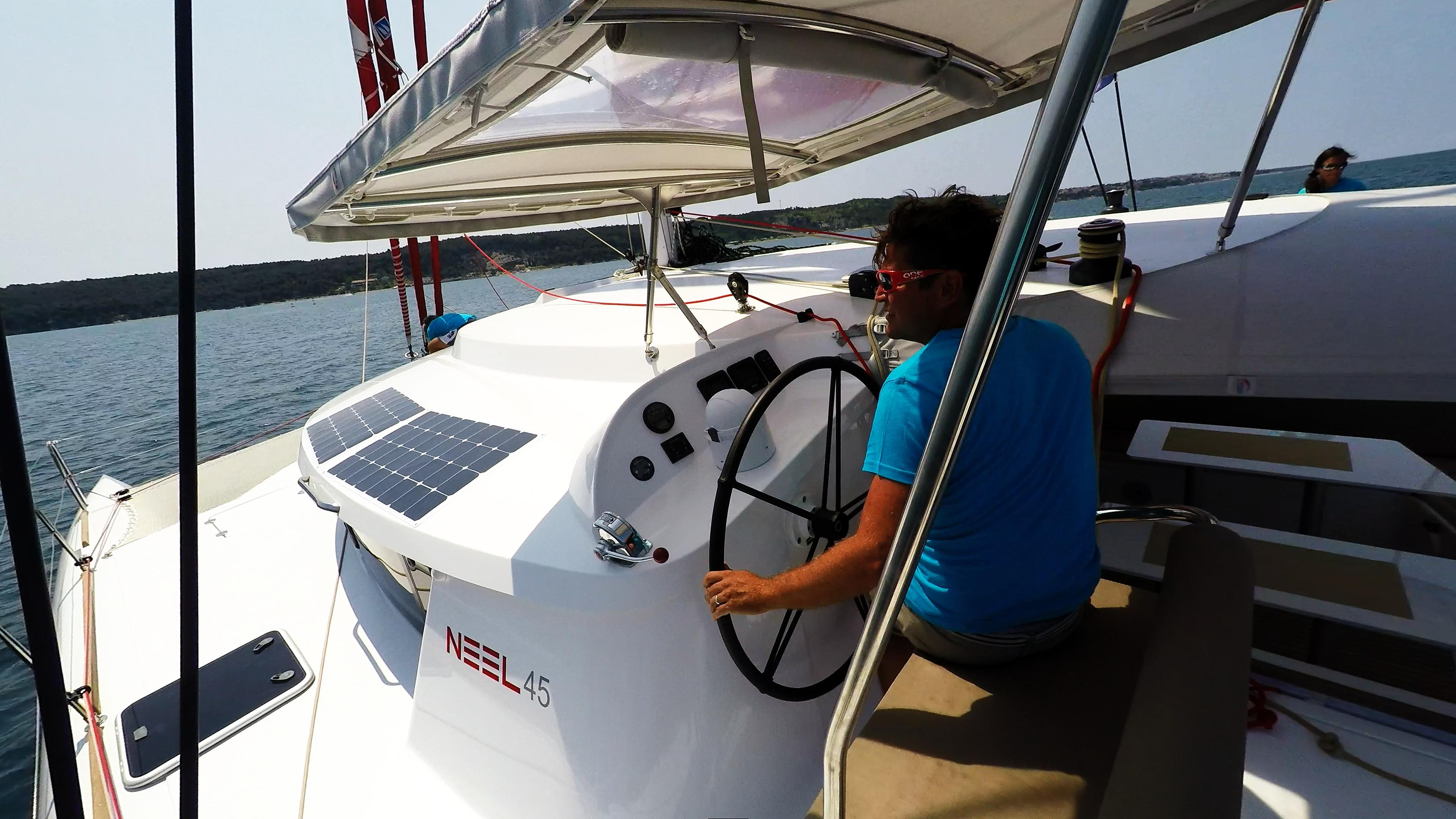 skipper in cockpit of trimaran sailing yacht neel 45