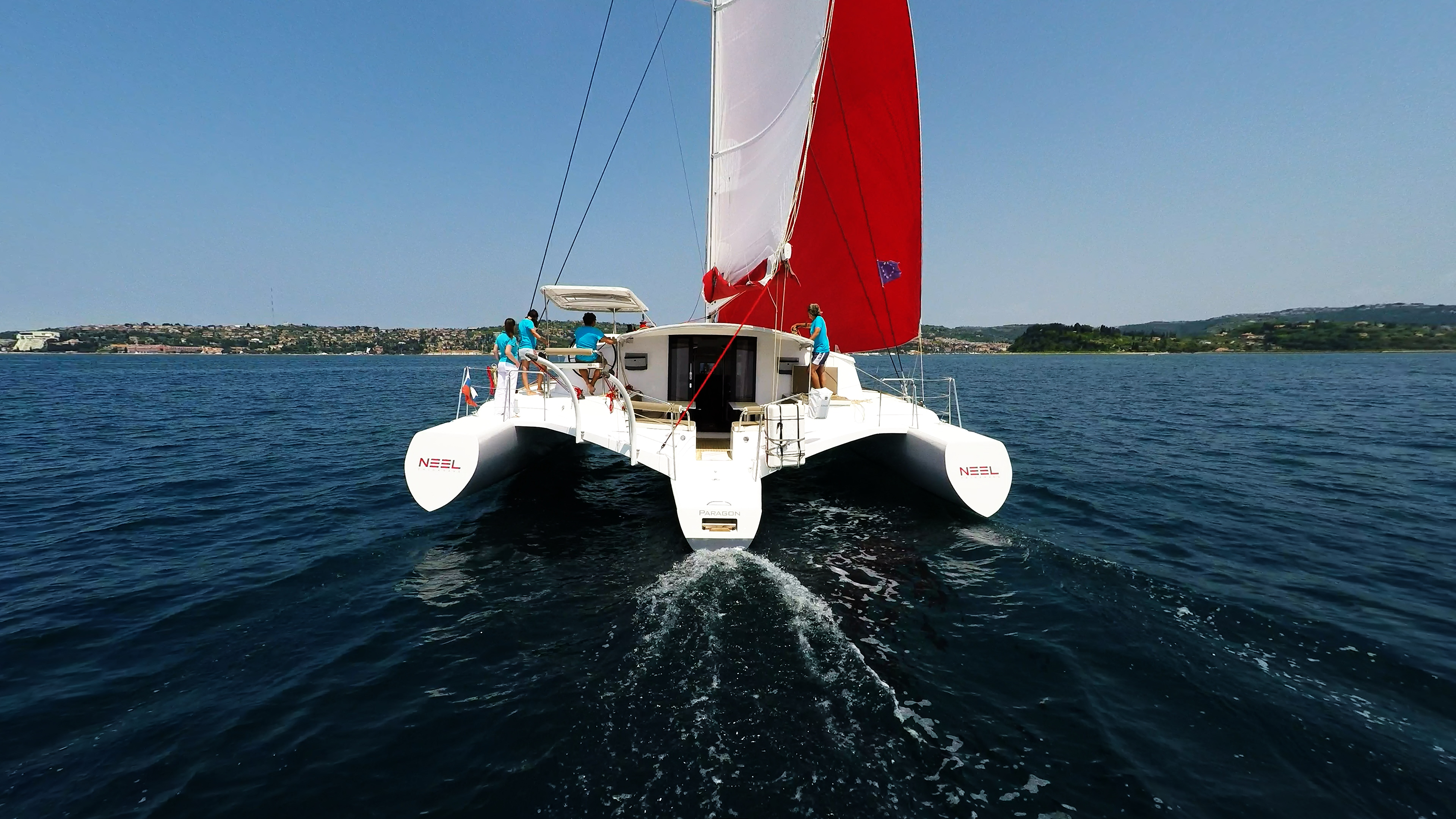 stern view of trimaran multihull yacht sailing