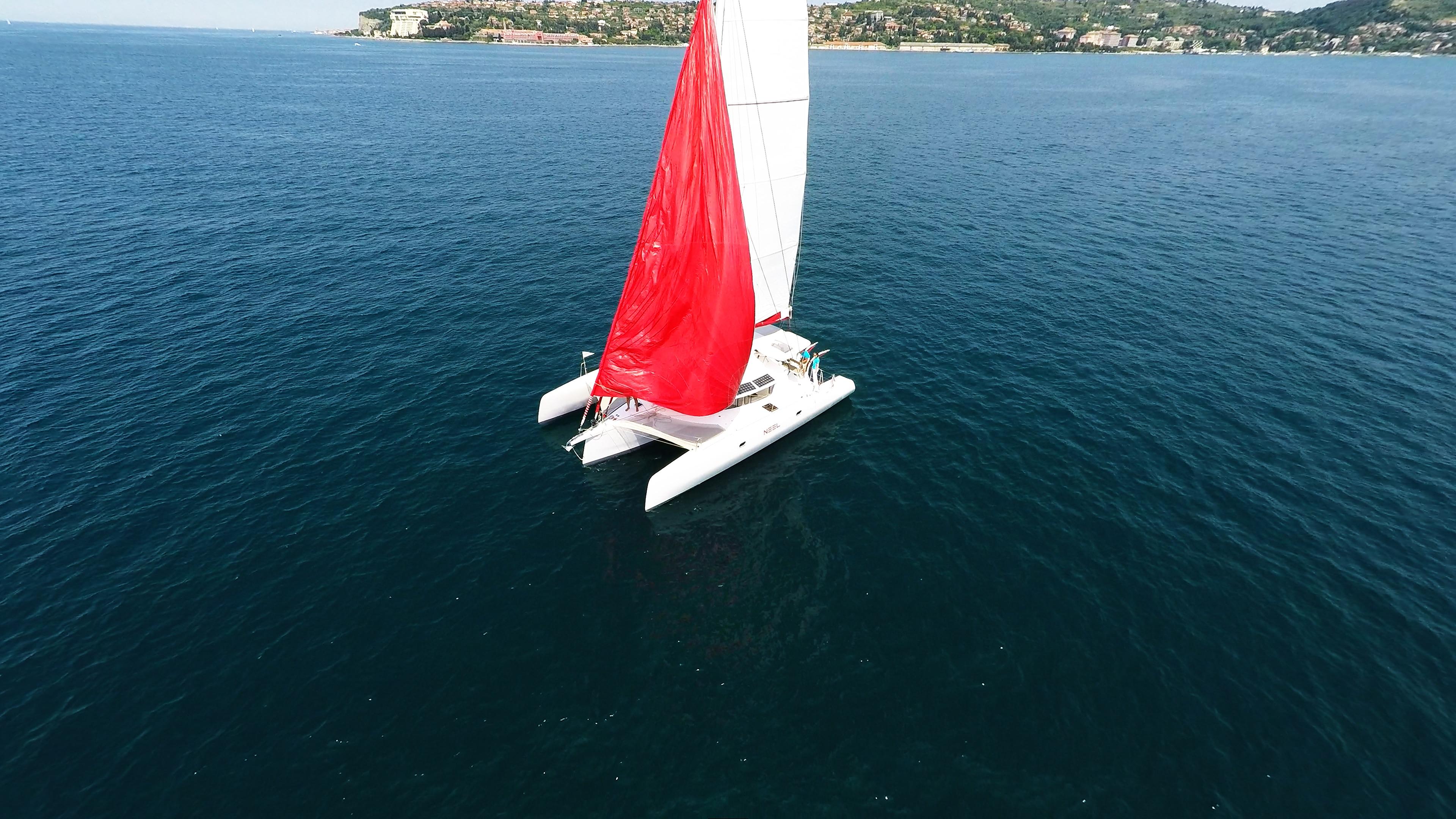 trimaran aerial photo hoisting red gennaker sail yacht