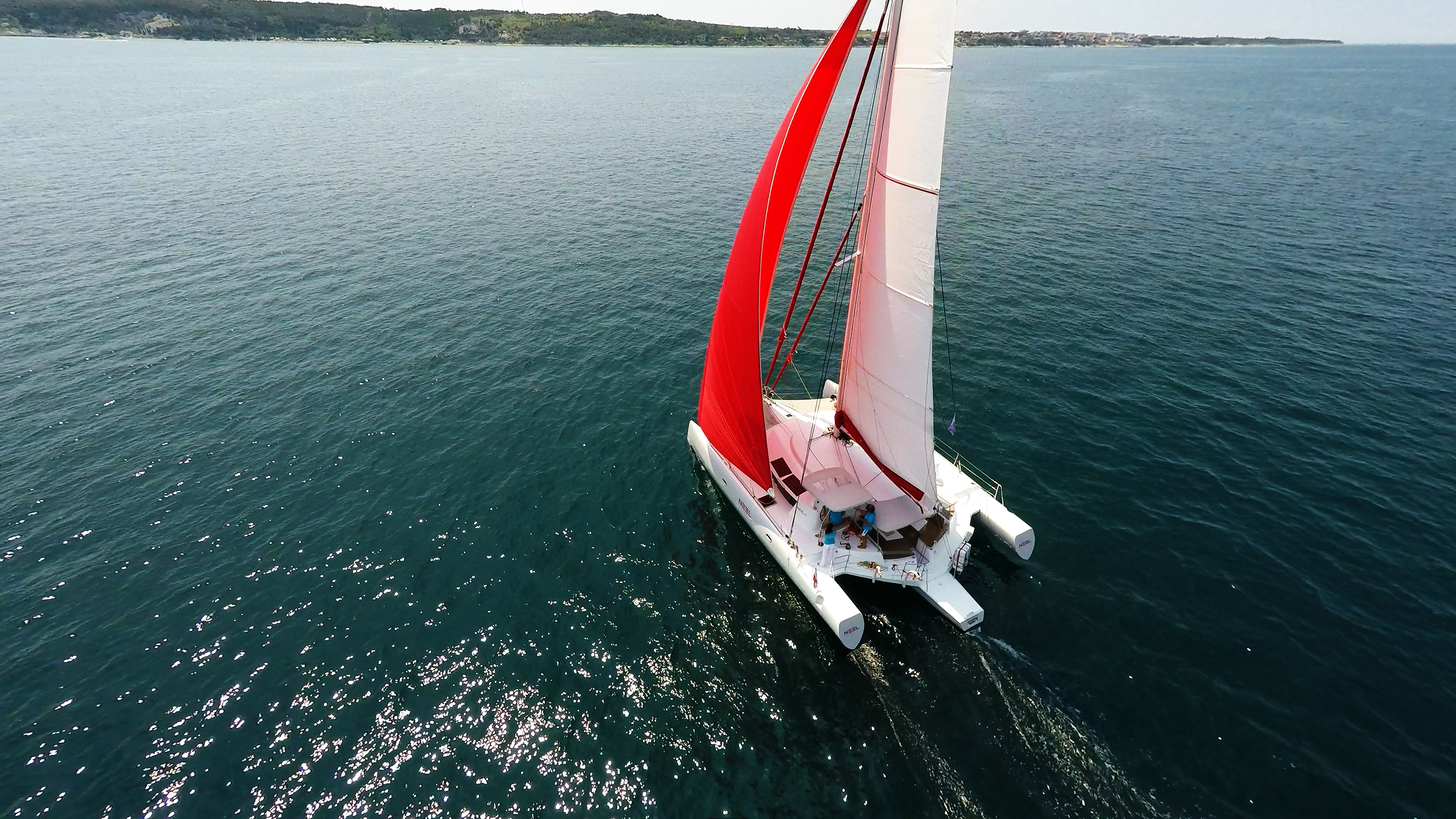 trimaran from above red gennaker crew in turquoise t-shirts sailing