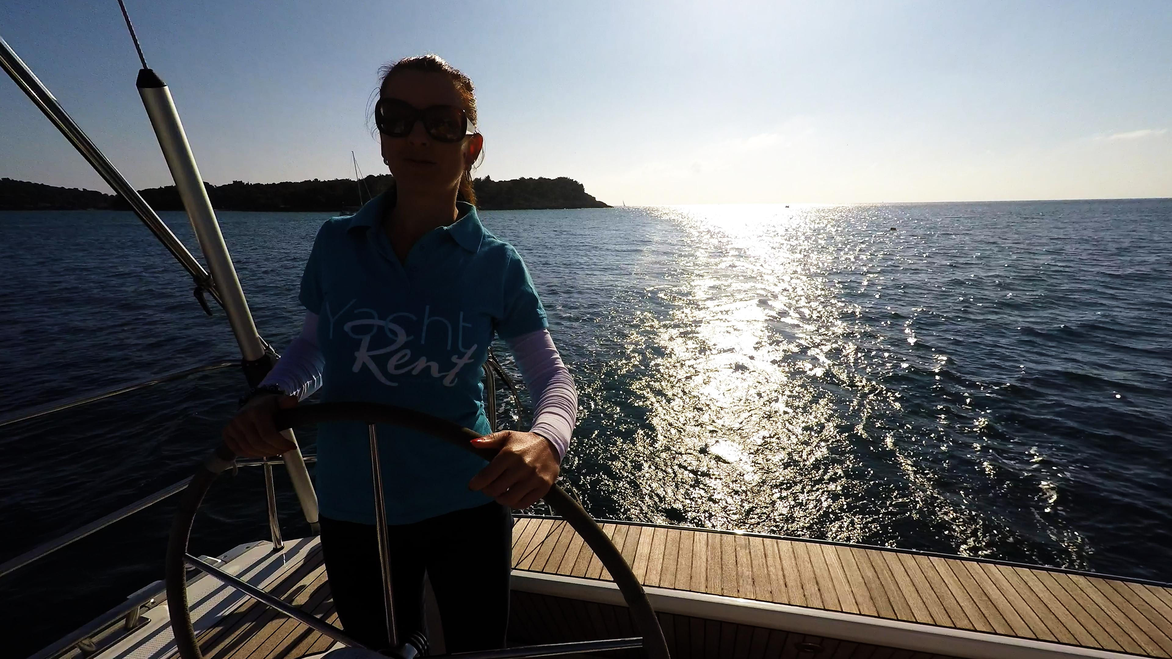 sailing yacht skipper at steering wheel of sailing yacht sun