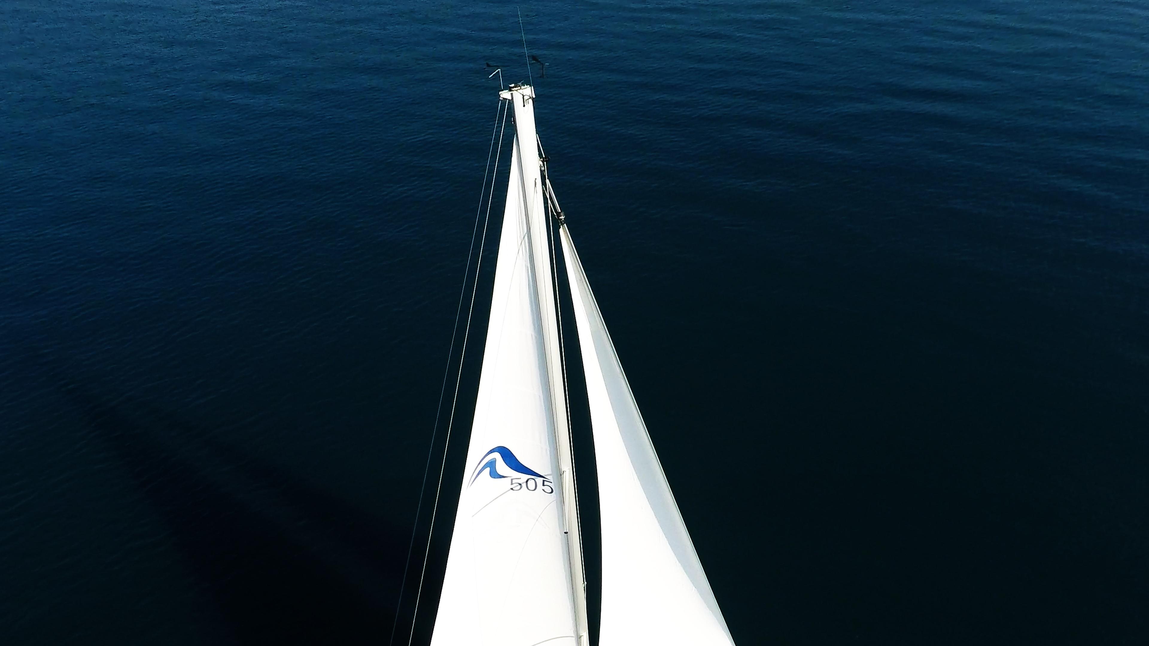 sailing yacht top of mast with main sail and genoa on sailing yacht